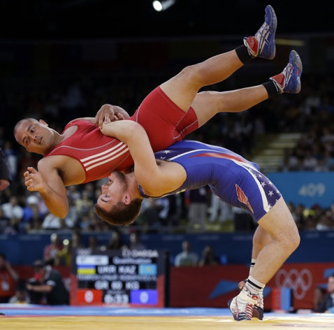 FILE - In this Monday, Aug. 6, 2012 file photo Keitani Graham of Micronesia competes against Charles Edward Betts of the United States, right, during the 84-kg Greco-Roman wrestling competition at the 2012 Summer Olympics, in London. An official familiar with the decision says IOC leaders have dropped wrestling from the program for the 2020 Olympics. In a surprise decision Tuesday Feb. 12, 2013, the official tells The Associated Press that the IOC executive board decided to retain modern…
