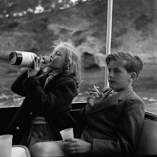 """The thirteen-year-old Princess Yvonne Sayn-Wittgenstein-Sayn takes a swig from a bottle while Prince Alexander, just twelve, sits with a half-smoked cigarette. Taken aboard the yacht of Bartholomé March off Majorca in 1955, the photographer was Princess Marianne """"Manni"""" Sayn-Wittgenstein-Sayn — the mother of Yvonne and Alexander — who's known by her photographic soubriquet of """"Mamarazza""""."""
