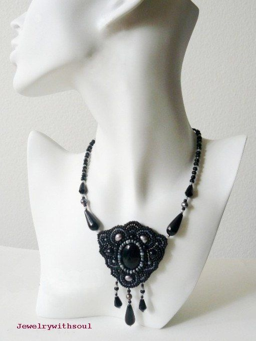 There is a black onyx cabochon of the center of this necklace embraced with different size seed beads, freshwater and glass pearls. Necklace part and fringe is made with seed beads, freshwater pearls and Czech glass teardrops. Clasp is dark silver tone with detailed leaf design. Embroidery part is neatly backed with soft, black ultrasuede. The whole necklace including clasp is approximately 19 inches (48cm) long with central part hanging down 3 3/4 inches (9,5cm) long, when measured with...