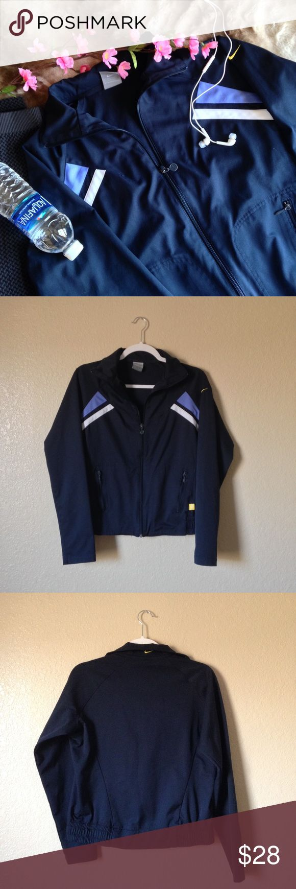 Nike Zip-Up Athletic Jacket Super cute Nike windbreaker/jacket, in a classic navy blue with light blue and white stripes near the shoulders, features two front zipper pockets and elastic waist. Very flattering fit. In great gently used condition, only sign of wear is the paint on the zippers is a bit faded. Size L. I accept reasonable offers ☺ Nike Jackets & Coats