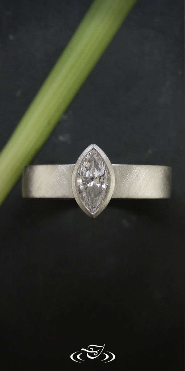 Custom Platinum minimalist mounting with full bezel setting for client provided 0.47ct Marquise diamond.