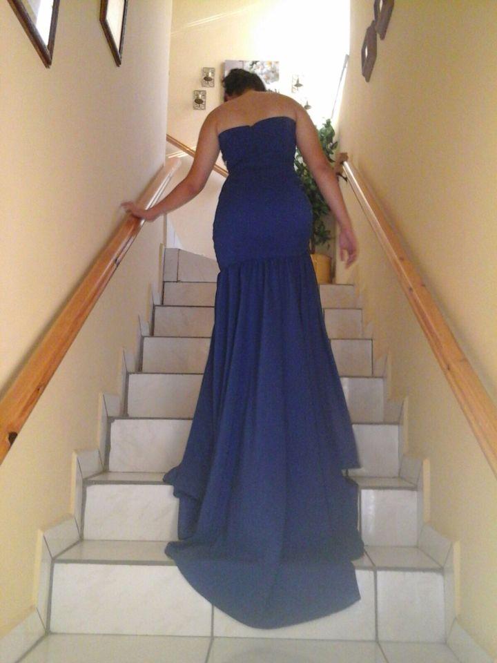 Vestido azul tipo sirena con cola larga.