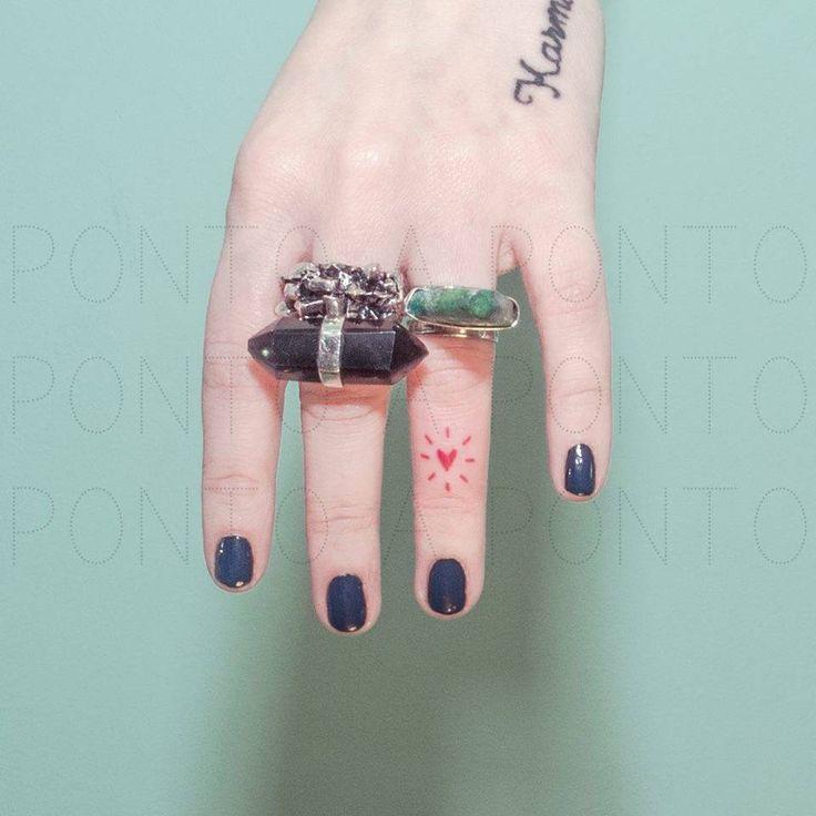 Tiny hand poked red heart tattoo on the left ring finger. Tattoo artist: Nano · Ponto a Ponto