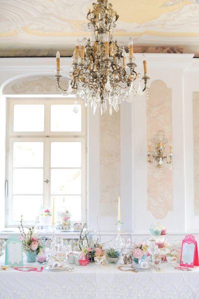 Lámpara de araña sobre decoración blanca y tonos pastel.