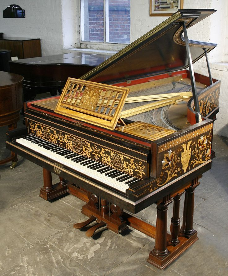 This Broadwood grand piano was designed by T G Jackson and inlaid by C H Bessant Faber. It was made for Athelstan Riley's Music Gallery at 2 Kensington Court London in 1892. Inlaid with scrolling foliage and pelter shields inscribed with 6 musical part-scores. Stand is american walnut with triplet pillars and carved scrolls. Keyboard has thick ivory fronts with turned arcading. Sharps inlaid with ebony and ivory.  http://www.besbrodepianos.co.uk/golden-age-of-pianos-exhibition.htm