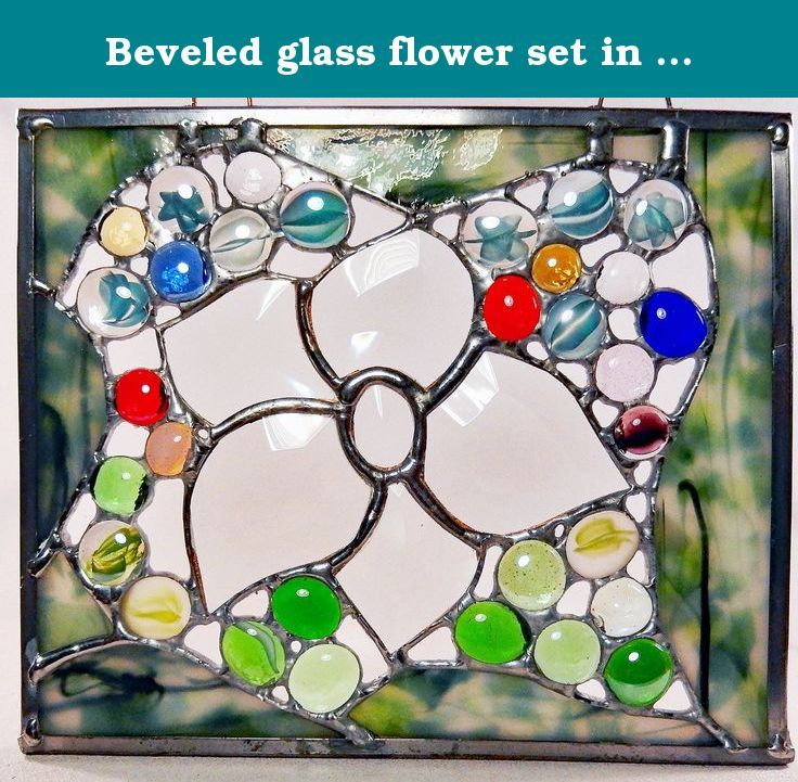 Beveled glass flower set in a bed of colorful, red, blue, yellow, green, glass jewels surrounded by handmade fractured/streamer glass. A large beveled glass flower is surrounded by many glass jewels in a variety of colors, such as red, blue, yellow, purple, green etc. I then incorporated vintage, handmade fractured/streamer glass for a frame which gives it the feel of nature. All is framed in lead with hangers attached, ready to enjoy. * Due to the nature of the fractured/streamer glass…