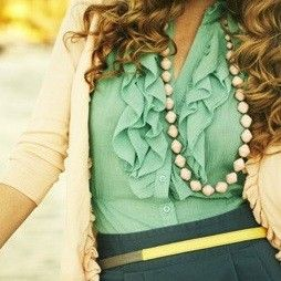 Ruffled green shirt, white cardigan, long necklace and a navy skirt.