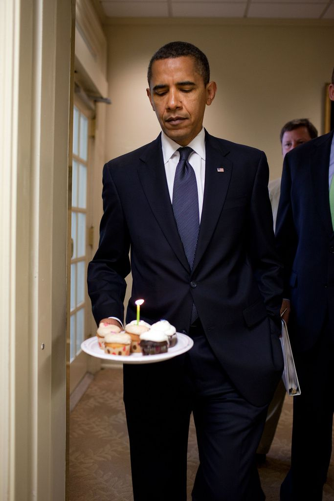 President Barack Obama watches the flame on the candle as he walks to the Brady Briefing Room to present cupcakes to Hearst White House columnist Helen Thomas in honor of her birthday, August 4, 2009. Thomas, who turned 89,  shares the same birthday as Obama, who turned 48 years old. (Official White House Photo by Pete Souza)