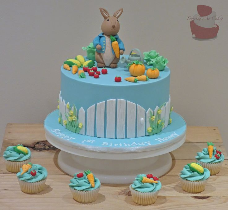 Peter Rabbit first birthday cake with matching cupcakes topped with vegetables from Peter Rabbits garden. Find me on Facebook (Driving Me Cakey) for more photos of my work or contact me via e-mail, drivingmecakey@gm... to enquire about an order. Located Fairview Park, South Australia.