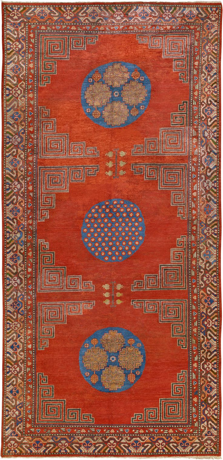 An antique silk Samarkand (Khotan) rug from the early 20th century, the open orange-red field around three blue roundels--one with scattered fleurons and the others with pomegranate motifs each framed by key patterns within a polychrome hooked motif border.Watch full size video of A silk Samarkand rug, Circa 1900, ID BB4577 - Video@ABC