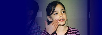Cued speech & Down Sydrome---Photo:Deaf kindergartener cueing a word starting with a vowel, probably 'e' after her teacher