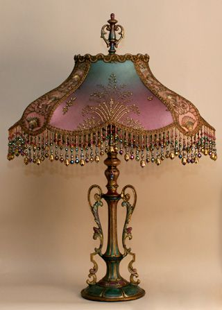 Antique 1920s era metal lamp base has been hand-painted. Hand-dyed Turkish Starling silk lampshade, dyed from pale teal into deep mauve and covered on the sides with gold metallic net with turquoise swirls. Front panels are covered in an exquisitely detailed gold beaded metallic net. Small panels are embellished with beautiful Nouveau/Egyptian style gold embroidered netting. Victorian era chenille and metallic trim crown the top of the shade. The hand beaded fringe is in matching tones…