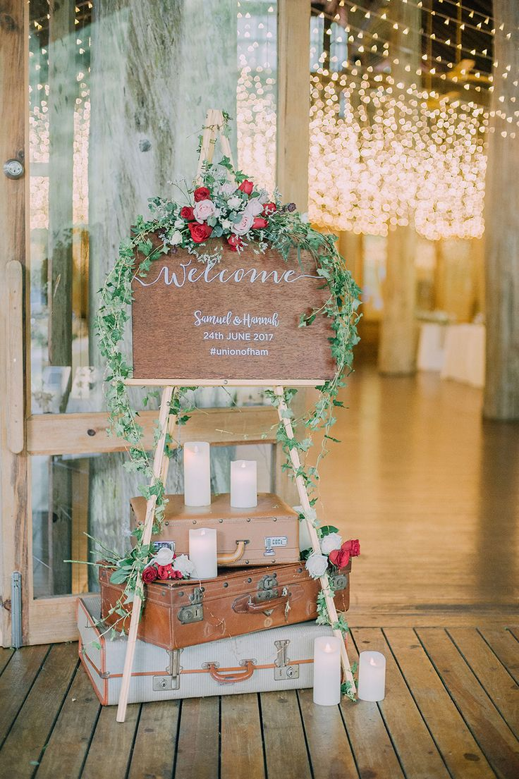 A rustic bohemian wooden sign with red and pink florals complimented by creeping greenery // Prior their hotel wedding reception in Kuala Lumpur, Samuel and Hannah got married before family and a fun, motley crew of their friends at Tanarimba, Janda Baik. Shot by Daren Chong Photography and planned by Pretty Little Things, the couple's Malaysia wedding featured a rustic bohemian theme befitting of the venue.