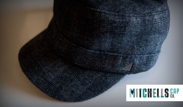 Mens Custom Winter Wholesale Hats : Mens Castro Cap in a jacquard print fabric and metal embossed branding. Black and grey print in a thick wool.