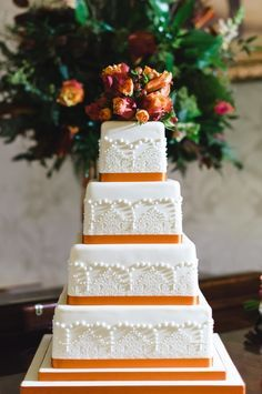 Unique square shaped wedding cake with hints of orange: www.stylemepretty... | Photography: Rachel Red - rachelredphotogra...