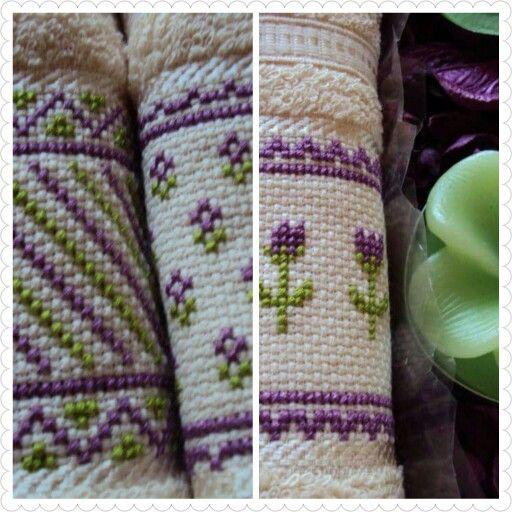 Juego de tres toallas bordadas en punto cruz con diseños geométricos y flores en tono lila.
