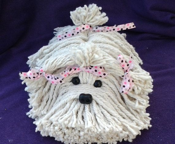 Adorable puppy dog made from a mop head. Cute dog nose and black eyes. Has pink ribbons with polka dots that are gray, pink, and black, tied on