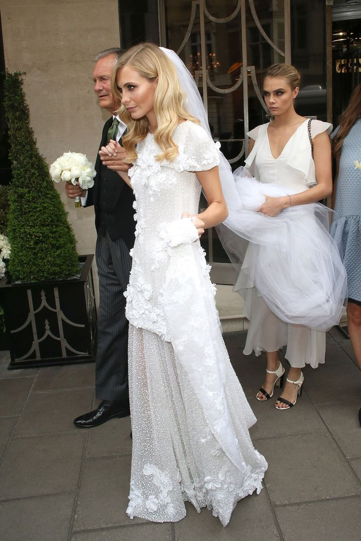 Poppy Delevingne married James Cook in London. The bride wore a stunning Chanel Haute Couture gown by Karl Lagerfeld with floral appliques, a cap sleeve and drop waist. Delevingne wore her hair down with a slight wave and long veil while her bridesmaid - sister Cara Delevingne - was also dressed in Chanel.