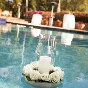 Floating pool decor of flowers, glass vase and pillar candles