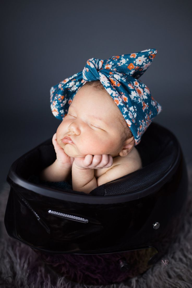 Newborn Profile portrait in color of baby girl in her dad's motorcycle helmet taken by Nature's Reward Photography