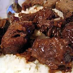 Sirloin strips are marinated in Worcestershire sauce and mustard, fried with onions and garlic, and served over rice.