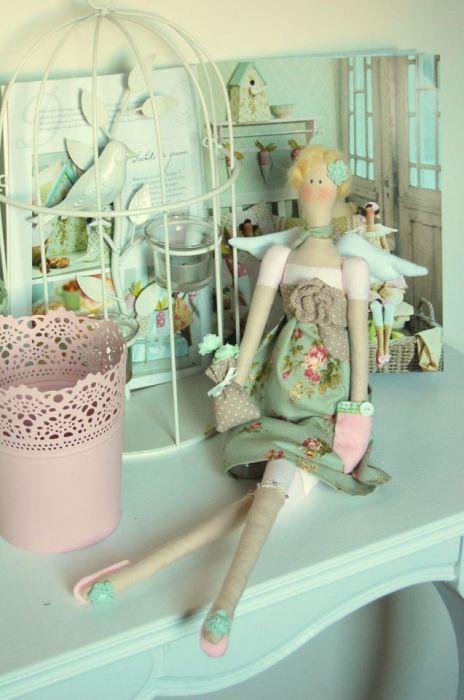 Lalka tilda wykonana z bawełnianych tkanin, utrzymana w pastelowej kolorystyce (róż,mięta,beże).  Zdobiona uroczymi dodatkami: koronka, koraliki, kokardki, woreczek, kieszonka filcowa, chusta na włosach. Włosy wykonane z włóczki czesankowej, wypełnienie lalki - silikonowe. Wysokość lalki - ok.50 cm.