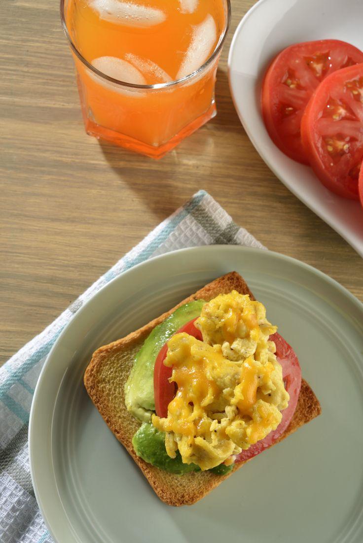 Delicioso desayuno de pan tostado con aguacate, jitomate y huevo revuelto con queso cheddar. Esta receta fácil de huevo es perfecta para comenzar el día con algo sabroso y muy sencillo de preparar.