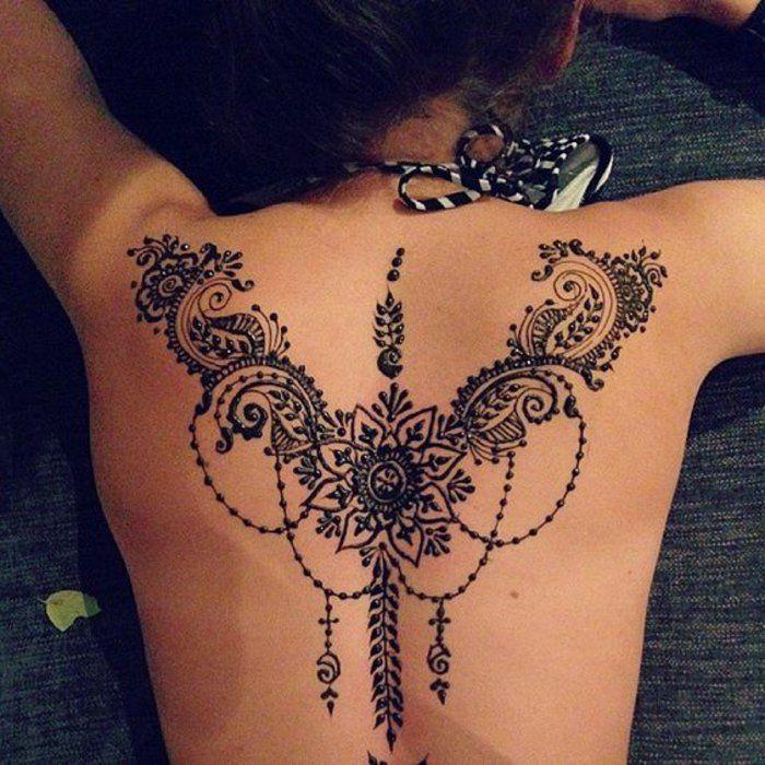 Frau mit tätowiertem Rücken, schwarzes Mandala Tattoo am Rücken, schwarz weißer Badeanzug für Frauen