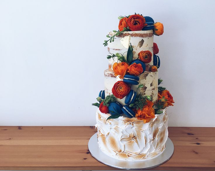 3 tier buttercream white wedding cake - two top tier semi naked white buttercream with bottom tier covered in toasted meringue. Orange & navy blue colour theme with gold foil detail #haranspatisserie