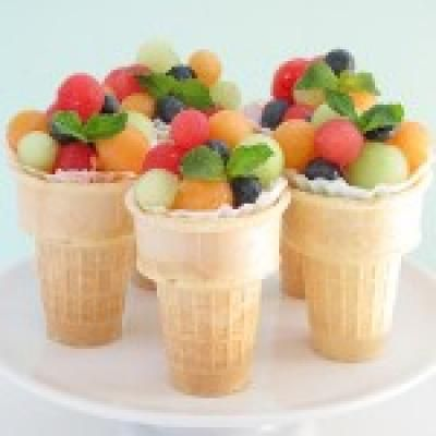 Fill bottom of cones with Skittles, put fruit in a cupcake wrapper and put in cones to serve! Love it!