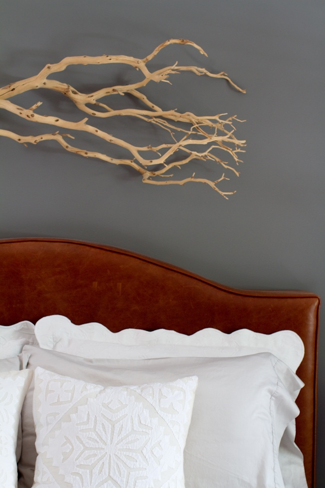 gray walls, white bedding, cognac leather headboard. tree branch is the coolest though