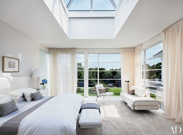 The skylit master bedroom has floor-to-ceiling windows with sheer curtains.
