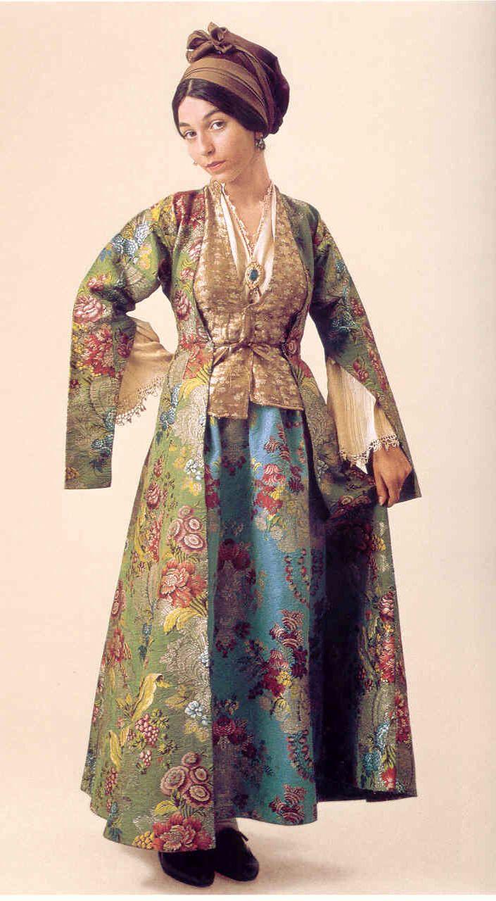 Πελοποννησιακό Λαογραφικό Ιδρυμα Φορεσιά από την Σιφνο. 18ος αιώνας. Το χρυσοφόρο στην αρχαιότητα νησί, φημισμένο για τους κεραμείς του, δεν θα μπορούσε να μη διακρίνεται από μια «χρυσή» φορεσιά. Η γυναικεία φορεσιά της Σίφνου αποτελείται από μια έσω βράκα, το λεγόμενο «μισοφόρι» ή «μεσοφούστανο». Ακολουθεί ένα λεπτό υποκάμισο,άσπρου χρώματος με ωραίο τελείωμα και κέντημα . Τη λινή και σταμπωτή φούστα τη λένε «καναλωτή» (επειδή έκανε κανάλια, λούκια). Αμάνικο γιλέκο, από λινό σταμπωτό, που…