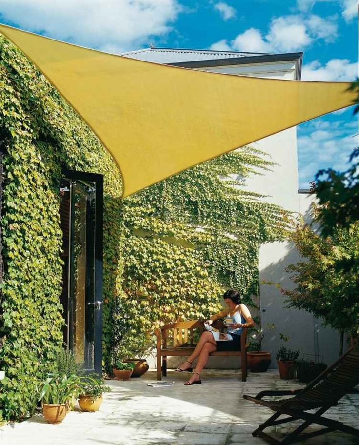 voile ombrage jaune de forme triangulaire sur la terrasse avec lierres
