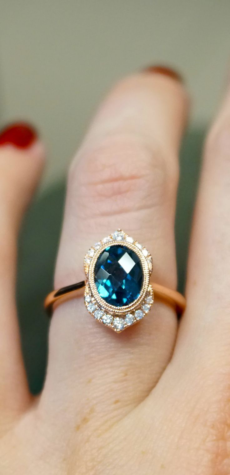 Custom modified diamond halo and London blue topaz 2-carat center with rose gold. Use a unique alternative center gem to be a little different and keep it affordable, too.    Joseph Jewelry | Bellevue | Seattle, WA | Designers of Fine Custom Jewelry