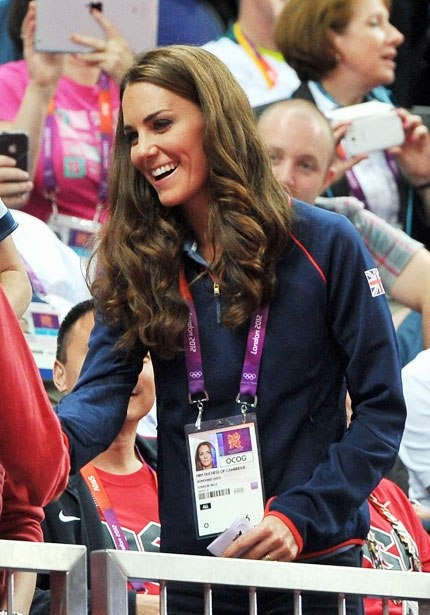 Cheering on handball on August 5, Kate swaps her usual white Team GB polo for a blue one, worn with jeans and (out of frame) bright-red sneakers. She carried a black Longchamp nylon bag, of the Le Pliage style