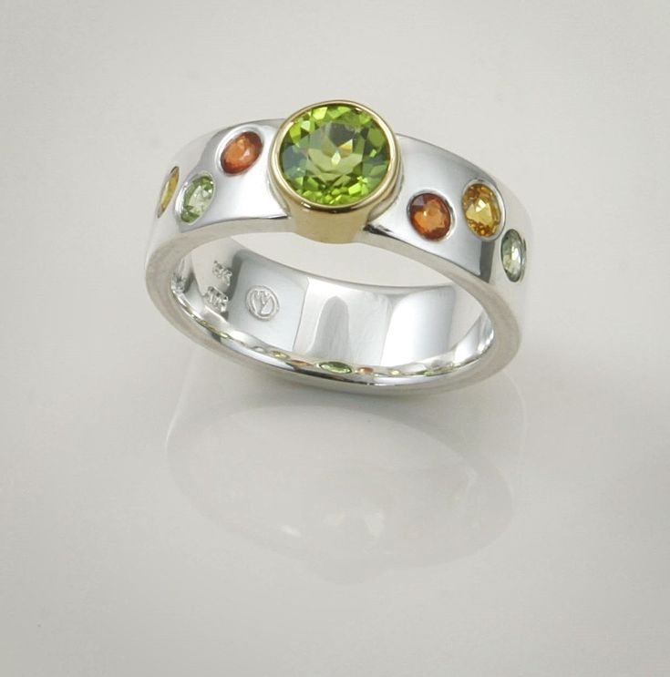 Ring: Peridot set in 18ct gold with flush set sapphires in the sterling silver band.