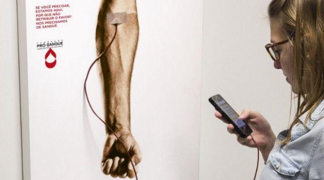 """Campaña para promover la donación de sangre en la que hay carteles para cargar el móvil con el siguiente mensaje: """"si lo necesitas estamos aquí para ti. ¿Por qué no devuelves el favor?. Necesitamos sangre"""