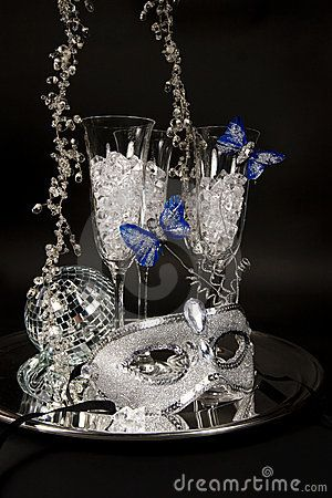 A shimmering silver mask trimmed with blue feather butterflies, a mirrored ball and champagne flutes filled with ice glass on silver party tray.