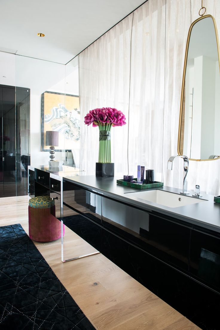 Black and white vanity with oblong mirror and tall purple flowers