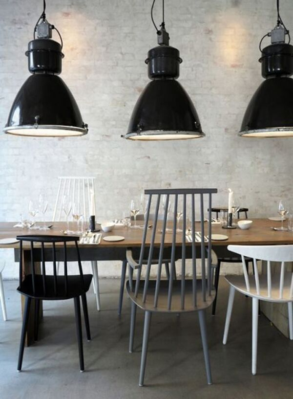 3 grote #zwarte #industriële #hanglampen boven een mooie houten #eettafel. Leuk met de verschillende #gekleurde #houten #stoelen. #black #pendant #lights #industrial