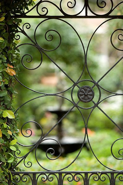 I love the pretty ironwork on the gate, with a view of the garden