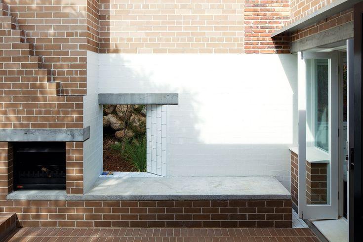 Owen + Vokes + Peters, Four Room Cottage, Brisbane. Walled brick courtyard, brick fireplace, painted brick