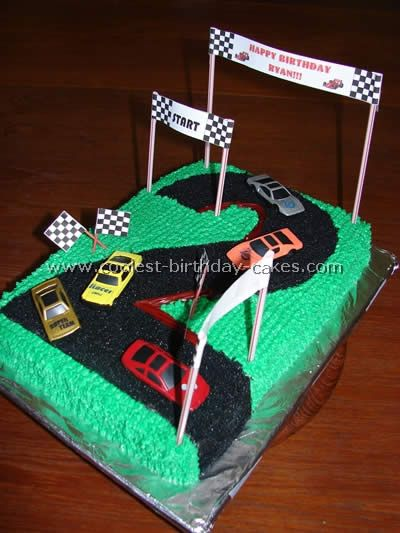"Race Track Cake found on a random site by someone named Leslie. I like the use of a sheet cake, the ""2"" and the banners. Have a LM car for the ""track""."