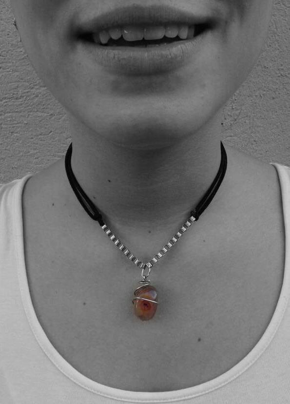 collar con cuerda de gamuza en color negro, piedra color marrón-anaranjado.