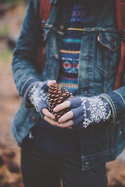 Holding a pinecone. Because winter picts here never include snow...