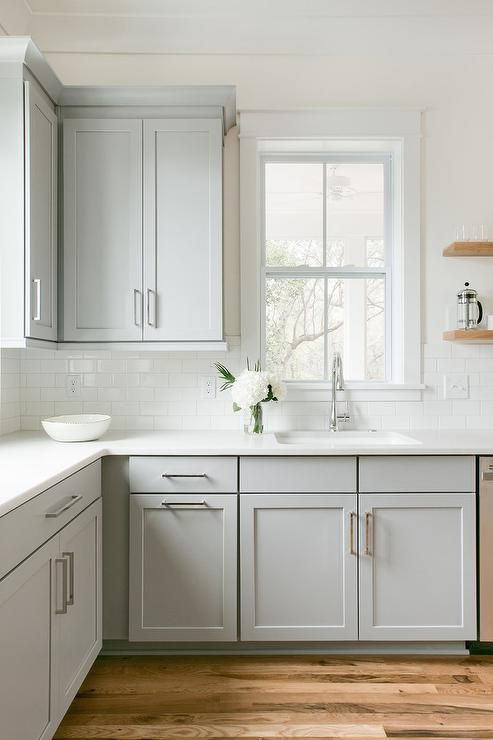 A Single Window In Transitional Kitchen Surrounds Dove Gray Shaker Cabinets With Floating Wood Shelves