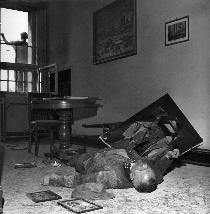 Lee Miller: Dead Volksturm General, Leipzig, Germany, 20th april 1945        A man in the uniform of a Volksturm (Home Guard) General lies dead on the floor the town hall office next to the suicided family of the Bürgermeister. Lee Miller's camera notes that outside the window, the scales of justice hang level.