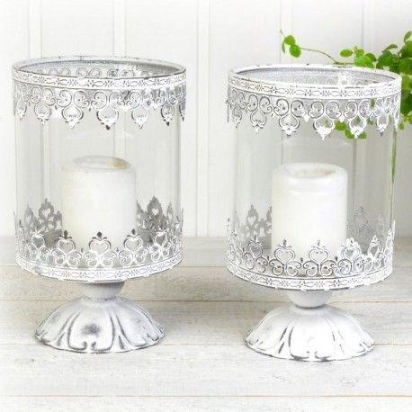 Två vackra ljushållare på fot i vitmålad metall som slipats för fin effekt. Varje lykta har varsin glascylinder och är avsedda för blockljus.
