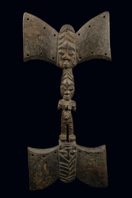 "wood, greyish black patina, handle in shape of a standing female figure, on both ends carved with a double-axe symbol with the bearded face of ""eshu"" in the middle, drilled holes around the rim, slightly dam., missing parts (breast, nose, double axe); such dance staffs were used likewise by men and women at ""shango"" celebrations. Their characteristic feature is the double axe symbol. ""Shango"" is associated with fertilizing rain, he is said to be truth-loving and should punish liars and…"